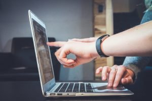 Two people pointing at open laptop screen