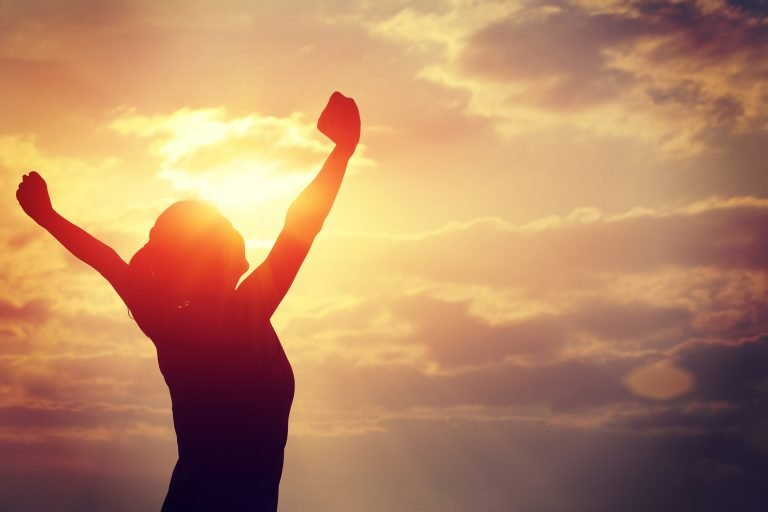 Picture of a woman, arms upraised with sunrise in background