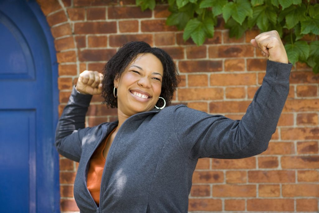 Picture of Empowered African woman with showing strong arms